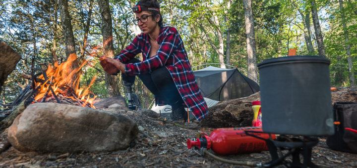 Angelina at the camp fire with an MSR Whisperlite Universal camp stove cooking dinner. Boundless Journey Photography.